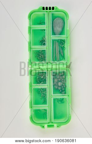 Plastic box with fishing tackles. Green container with fishing hooks, white background.