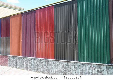 Stacks of various colorful metal fence panels and metal roof sheets for sale. Building and construction materials colored steel roof tiles for sale.