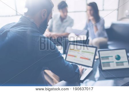 Three partners making research for new business direction.Young businessman working modern laptop and showing documents to young colleague.Business people meeting concept.Blurred background