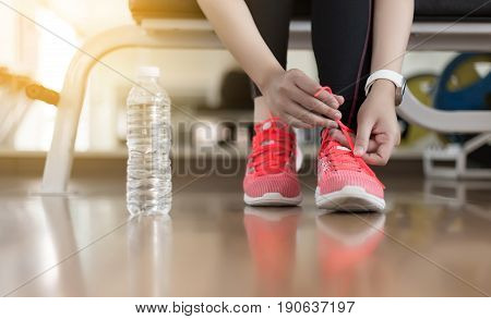 Woman Runner Tying Her Shoelaces  Fitness Exercise In Gym