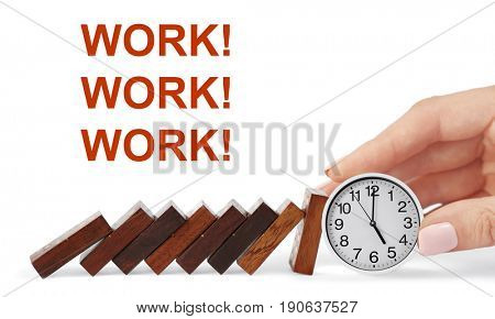 Falling dominoes and female hand holding clock on white background. Concept of work time