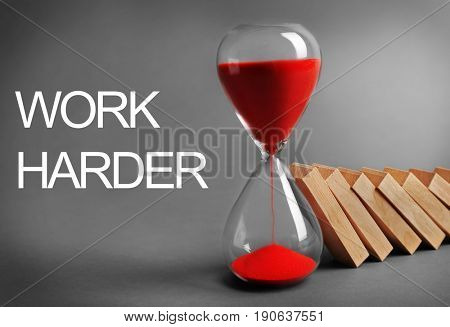 Hourglass with falling dominoes and text WORK HARDER on gray background. Business concept