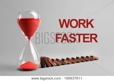 Hourglass with falling dominoes and text WORK FASTER on gray background. Business concept