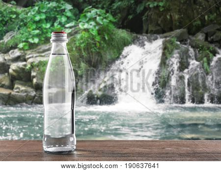 Glass bottle of clear water on landscape background