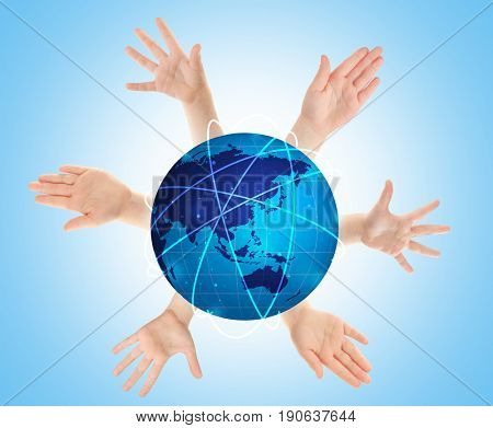 Children's hands surrounding globe on blue background. Concept of worldwide unity and environment protection