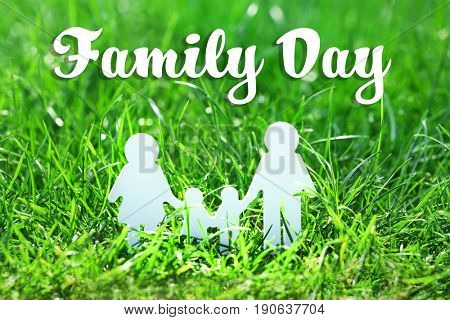 Figure of parents with kids on green grass. Family day concept
