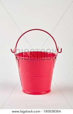 Red bucket on white background. Empty household pail for gardening.