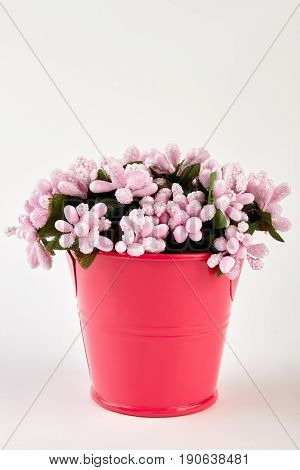 Decorative artificial flowers in bucket. Pink blossom bouquet in red bucket on white background.