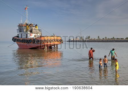 Bandar Abbas Hormozgan Province Iran - 16 april 2017: The tugboat ran aground the shore the sailors leave for the land they pass by three young children who playing in shallow water.