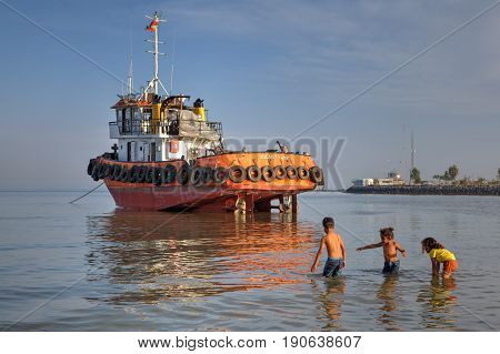 Bandar Abbas Hormozgan Province Iran - 16 april 2017: Three young children two small girls and one boy about seven years old play in shallow water near tugboat who ran aground.