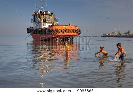 Bandar Abbas Hormozgan Province Iran - 16 april 2017: Three children play outdoors swimming in the shallow water of the Persian Gulf in the evening sun next to a stranded tug.