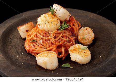 Pasta with fried scallops, oregano and tomato sauce on black wooden plate, close-up
