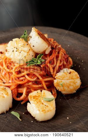 Steamy hot pasta with fried scallops and tomato sauce on black wooden plate