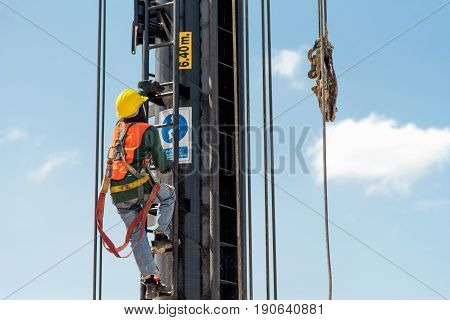 Construction workers wearing safety harness and adequate safety gear while working at high level at the construction site
