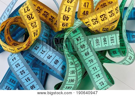 Heap of measuring tapes. Different measuring tapes, white background.