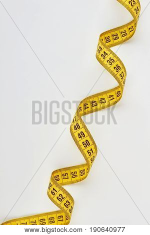 Yellow swirly measuring tape. Vertical image of measurement tool.