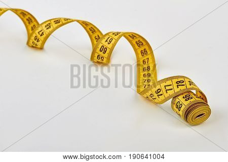 Spirally shape measuring tape. Rolled measuring tape isolated.
