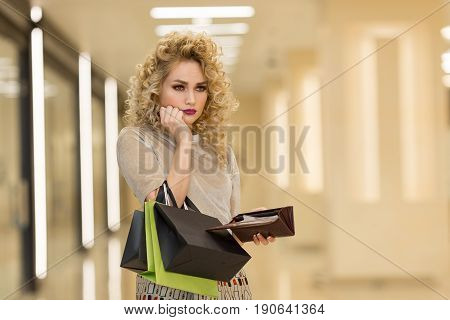 Portrait Of Unhappy Young Woman Looking In Her Wallet In Shopping Center, Spent Too Much, Not Enough