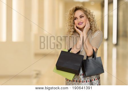 Woman Surprise Holds Cheeks By Hand .beautiful Girl With Shopping Bags Pointing To Looking Left. Pre