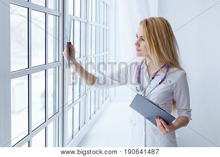 Young Smiling Female Doctor With Stethoscope Looking At X-ray At Doctor's Office.