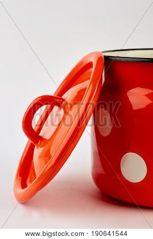 Cropped image of enameled dish. Household traditional dishware, white background. Red jug for milk in white points.