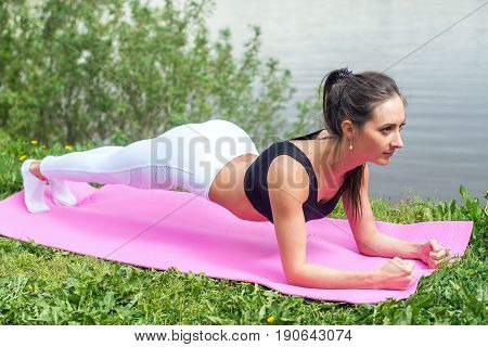 Fit woman doing elbow plank exercise working on abdominal muscles exercising the river coast.
