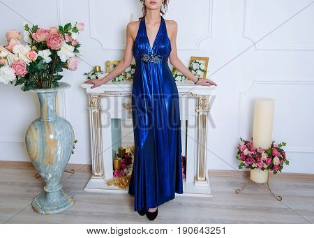 Young Beautiful Slim Brunette Girl In Long Blue Dress With Open Shoulders And Decollete Stands Near