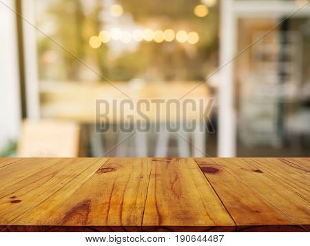 Wooden board empty table in front of blurred background. Perspective brown wood over blur in coffee shop or cafe- can be used for display or montage your products.Mock up your products.Vintage-filter.