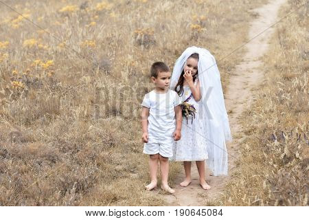 Young bride and groom playing wedding summer outdoor. Children like newlyweds. Little girl in bride white dress and veil with little boy groom. Bridal, wedding concept, image toned and noise added.