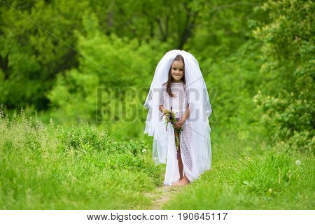 Young bride  playing wedding summer outdoor, newlyweds. Little girl in bride white dress and bridal veil posing over fresh greenery, kids game. Bridal, wedding concept