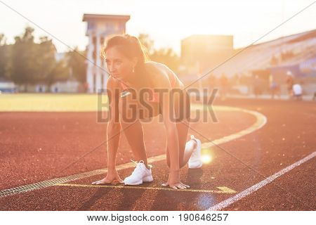 Woman in starting position ready for running in stadium