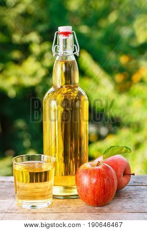 apple cider in glass and in bottle with fresh apples on wooden table with blurred natural background. Vertical shot. Summer drink