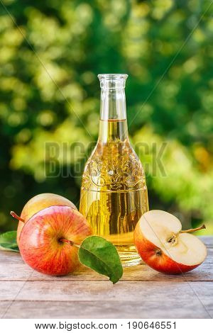 apple cider, juice or vinegar in glass bottle and ripe fresh apples on wooden table with blurred natural background. Vertical shot. Summer drink