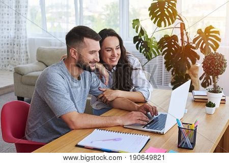 Wide shot of smiling couple surfing in laptop sitting at table