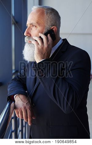 Vertical of bearded man talking on phone while looking out window and leaning on handrail