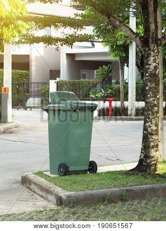 Large green trash bin for public park.