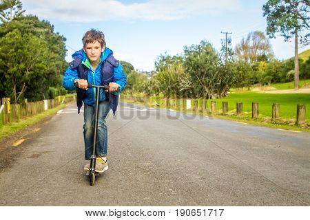 outdoor portrait of young happy preteen boy riding a scooter on natural background