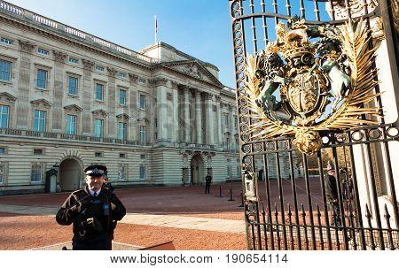 LONDON, ENGLAND UK - December 11, 2016: The Buckingham Palace and British police officers on duty on December 11, 2016, England UK.
