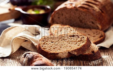 Slices of rustic sourdough spelled bread on wooden table