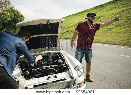 Man Hitch Hiking on The Street Side Near The Broke Down Car