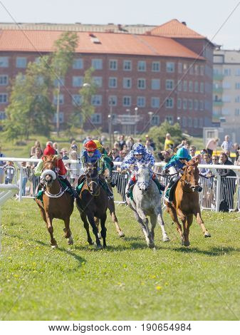 STOCKHOLM SWEDEN - JUNE 06 2017: Tough fight between colorful jockeys riding gallop arabian race horses at Nationaldags Galoppen at Gardet. June 6 2017 in Stockholm Sweden