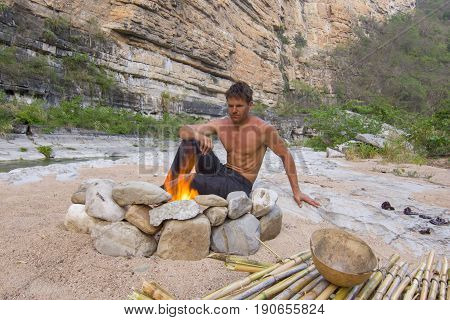 Muscular shirtless Caucasian man sitting at campfire in rugged Rio la Venta Canyon in Chiapas Mexico