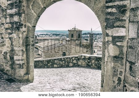 View from upper side to the centre of medieval Trujillo town under stone arch. Caceres Extremadura Spain