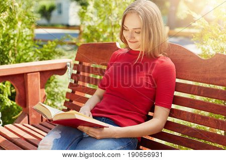 Restful woman with fair hair wearing red sweater and jeans sitting at wooden big bench holding book reading with pleasure. Student blonde female preparing for exams while sitting in green park