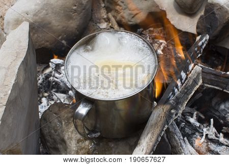 Aluminum cup with soup in a rolling boil sitting on a rock in a burning campfire
