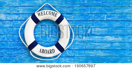 White Color Life Buoyancy With Welcome Aboard On It Hanging On Blue Wall. Had Space On Right Side Fo