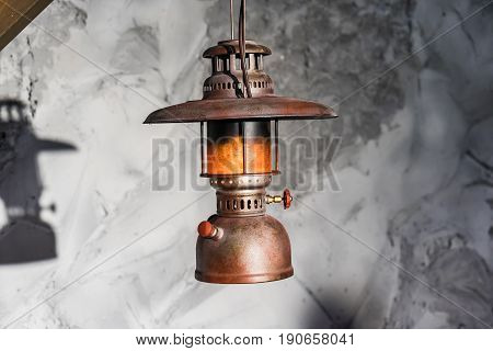Vintage kerosene oil Lantern lamp burning with a soft glow light and antique rustic stone wall