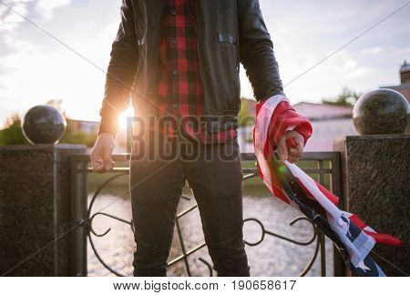Unrecognizable aggressive man with american flag on sunset background. Offence, disappointment in law, strike at work concept