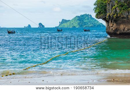 Three Wooden Thai Boats A Long Tail In The Sea Mooring To The Shore