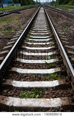 Summer. Railroad tracks go to the horizon. In the frame sleepers rubble stones poles green trees